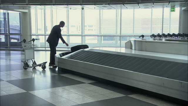 ws businessman removing suitcase from baggage claim carousel and putting on luggage cart / munich, germany - push cart stock videos & royalty-free footage