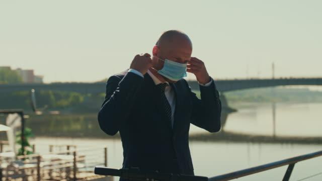 vídeos y material grabado en eventos de stock de empresario retorturándose scooter eléctrico y poniéndose mascarilla - ciclomotor vehículo de motor