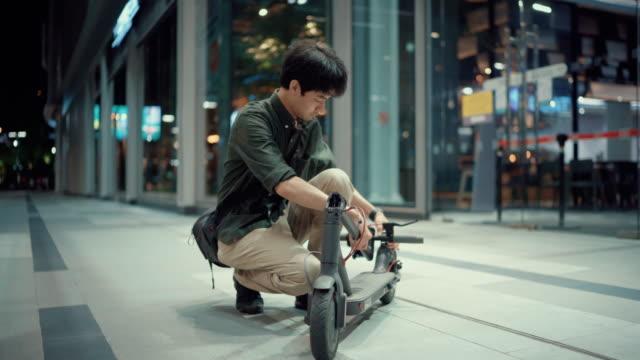 geschäftsmann fährt nachts mit einem e-scooter nach hause - motorroller stock-videos und b-roll-filmmaterial