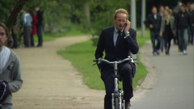 vídeos de stock, filmes e b-roll de ms cu selective focus businessman riding bike through park while talking on mobile phone / amsterdam, holland - traje completo