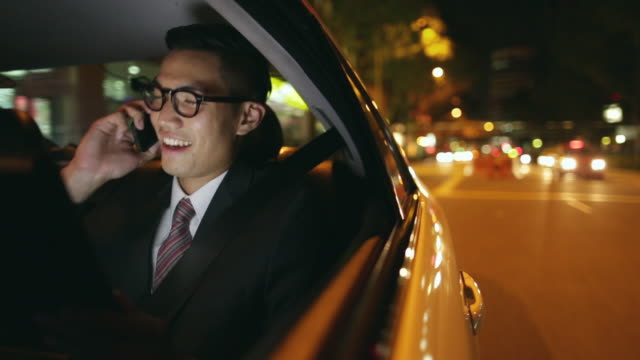 Businessman riding in the back seat of car, talking on the phone.