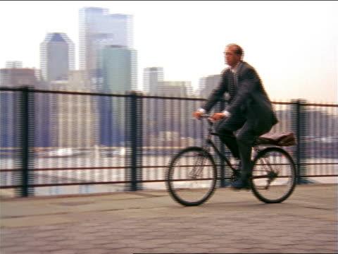 vídeos y material grabado en eventos de stock de pan businessman riding mountain bike by east river / city skyline in background / brooklyn heights - bicicleta vintage