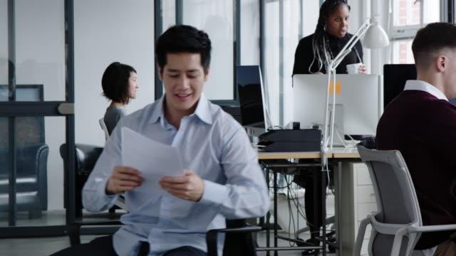 vídeos de stock, filmes e b-roll de empresário montando em sua cadeira giratória para entregar um documento no escritório - cadeira de escritório