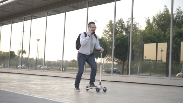 4K: Businessman Riding Push Scooter.