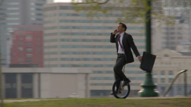 ws pan businessman riding through park and talking on mobile phone while riding unicycle/ richmond, virginia - aktentasche stock-videos und b-roll-filmmaterial