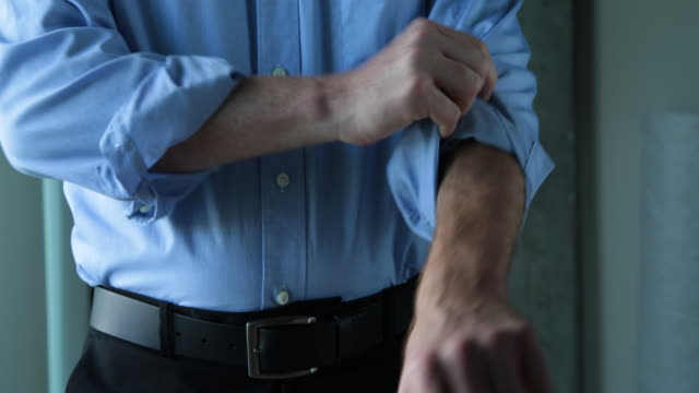 MS businessman rolling up shirt sleeve and crossing arms