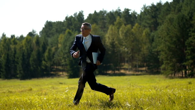 a businessman running across the field - button down shirt stock videos & royalty-free footage