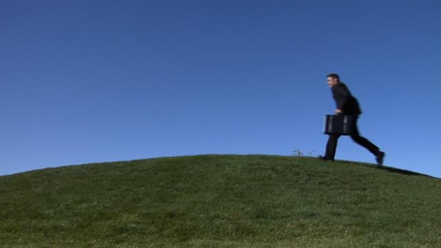 SLO MO, WS, Businessman running in field