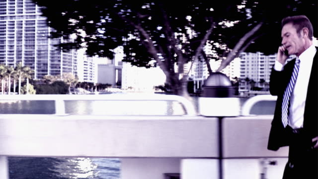 stockvideo's en b-roll-footage met slo mo cross process businessman running on bridge and talking on mobile phone, south beach, florida - driekwartlengte