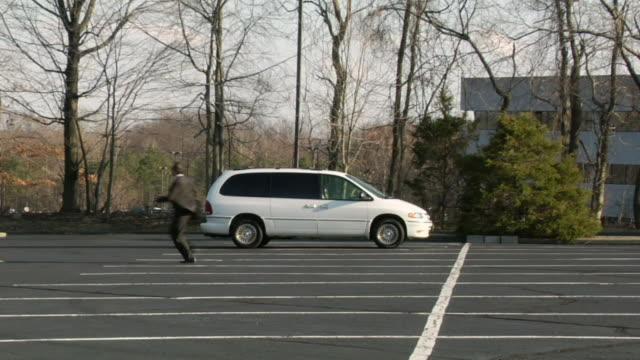 ws, businessman running on parking lot, upper saddle river, new jersey, usa - people carrier stock videos & royalty-free footage