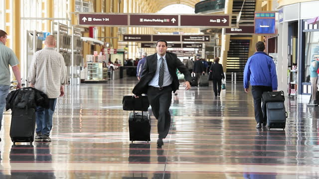 Businessman running through airport concourse