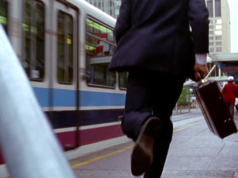 vídeos y material grabado en eventos de stock de businessman running to catch train - traje corbata