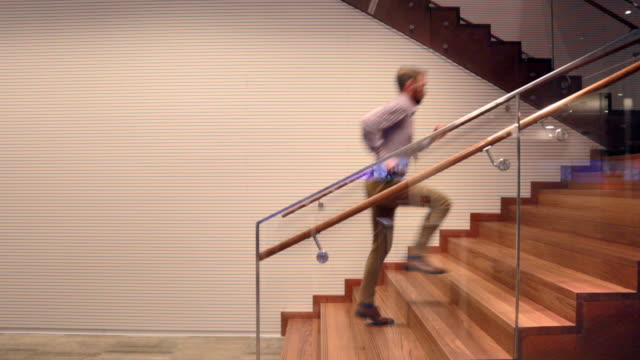businessman running up stairs inside - stock video - velocità video stock e b–roll