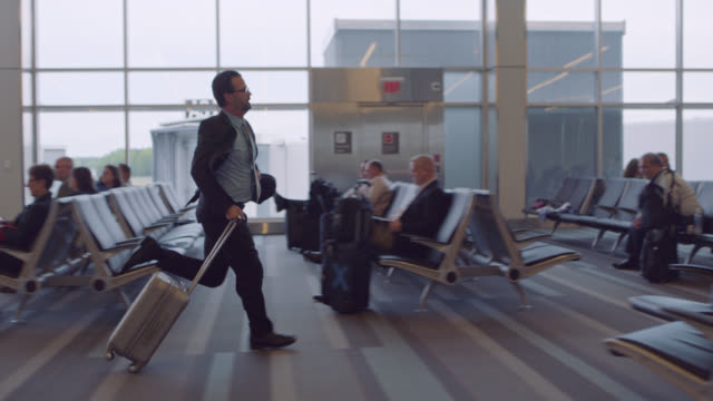 slo mo. businessman runs through crowded airport terminal waiting area. - sala d'imbarco video stock e b–roll