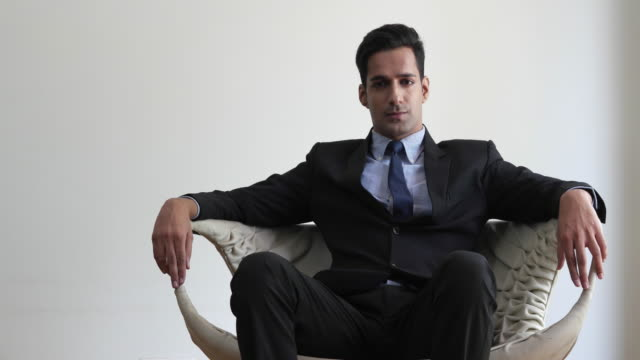 Businessman seated in an wide arm chair looking directly at the camera with arrogance and smug