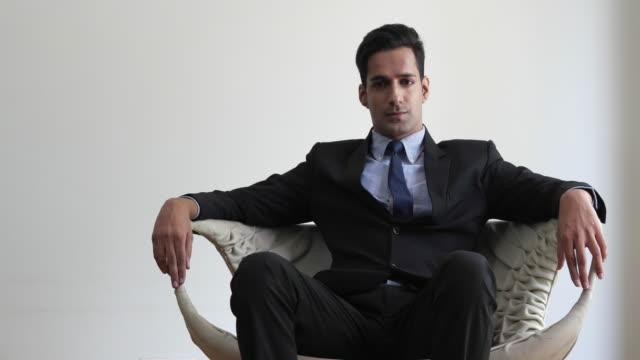 vídeos y material grabado en eventos de stock de businessman seated in an wide arm chair looking directly at the camera with arrogance and smug - sillón