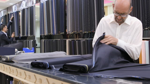 businessman selecting fabric for a custom made suit - customized stock videos and b-roll footage