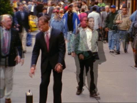 vídeos de stock, filmes e b-roll de businessman sets down briefcase, checks watch + walks slowly on sidewalk as time lapse people walk past him - 1999