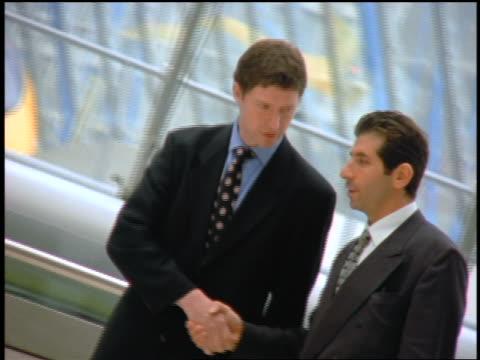2 businessman shaking hands + walking in Waterloo Underground station / crowd in foreground /  London