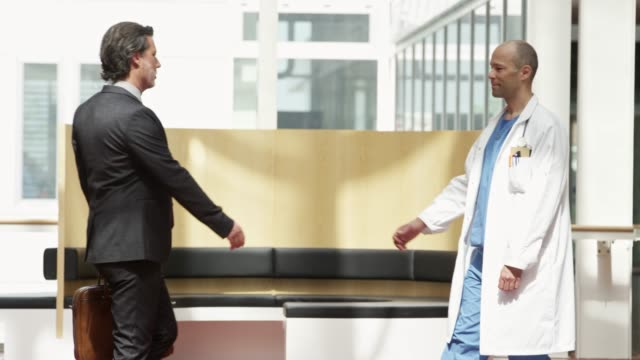 businessman shaking hands with doctor at hospital - salesman stock videos & royalty-free footage