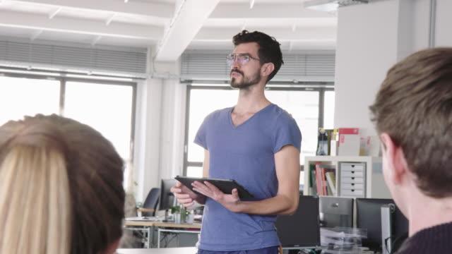 geschäftsmann teilt neuen businessplan mit team - arbeitskollege stock-videos und b-roll-filmmaterial