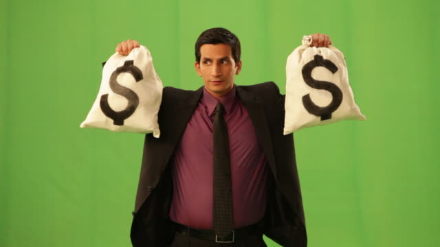 businessman showing a dollar sack  - lotterie stock-videos und b-roll-filmmaterial