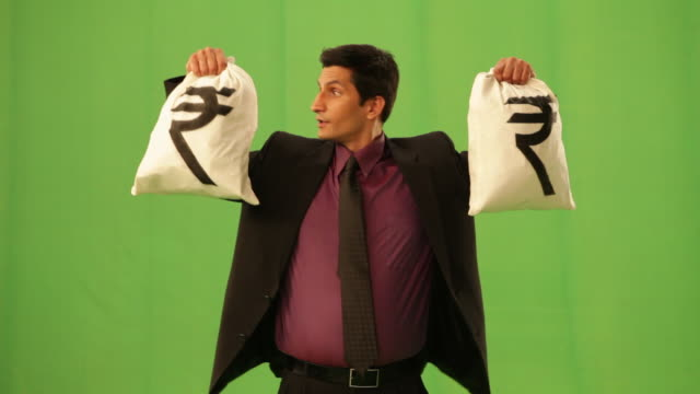 businessman showing a rupee sack  - geld verdienen stock-videos und b-roll-filmmaterial
