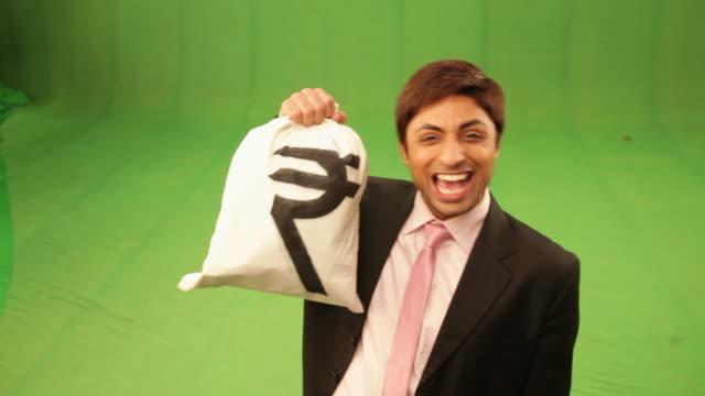 Businessman showing a rupee sack