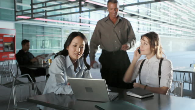 MS Businessman showing blueprint to businesswomen in cafeteria, Los Angeles, California, USA
