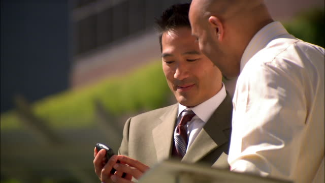 vídeos de stock e filmes b-roll de businessman showing co-worker smart phone while on break outside - camisa e gravata
