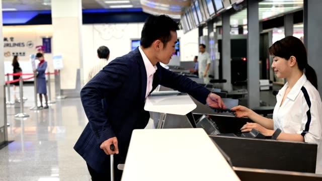 vídeos y material grabado en eventos de stock de empresario que muestra el billete electrónico en el aeropuerto - taiwán