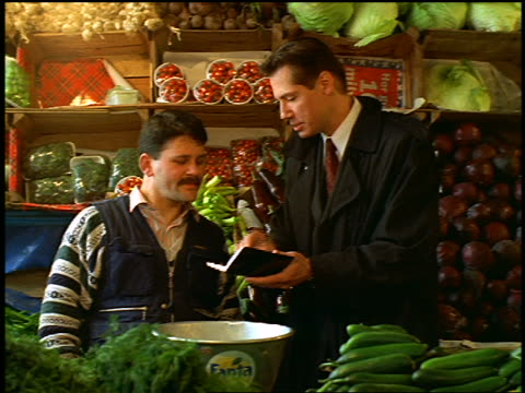 Businessman showing grocer something in small notebook then shaking hands with him