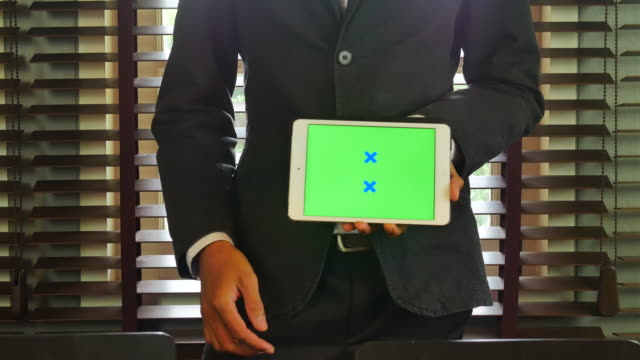 Businessman showing her digital table with a green screen