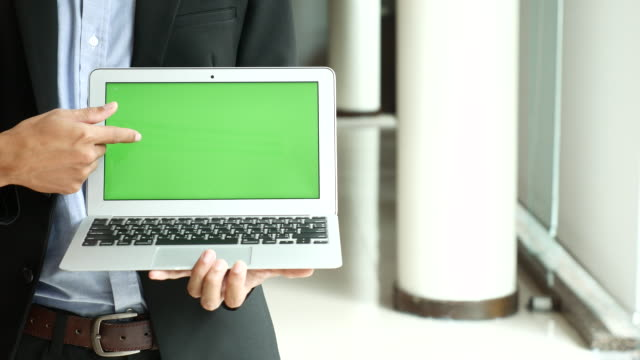 Businessman Showing Laptop with Green screen display,Chroma key