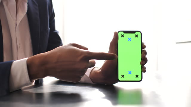 businessman showing smart phone with green screen - human finger stock videos and b-roll footage