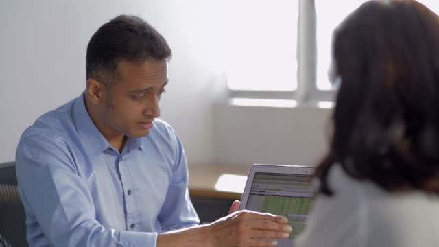 ms selective focus businessman shows his female colleague graphs on laptop / singapore - employee engagement stock videos & royalty-free footage