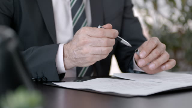 Businessman signing a document in his office