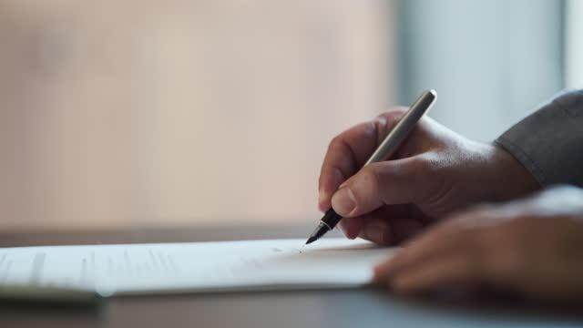 businessman signing legal paper in office - autograf bildbanksvideor och videomaterial från bakom kulisserna
