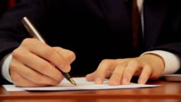 Businessman signs papers, contract, agreement, works on laptop