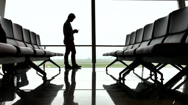空港でのビジネスマンシルエット電話、ビジネストラベル - ロビー点の映像素材/bロール