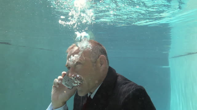 ws businessman sinking underwater in pool, using mobile phone / richmond, virginia, usa - sichtbarer atem stock-videos und b-roll-filmmaterial