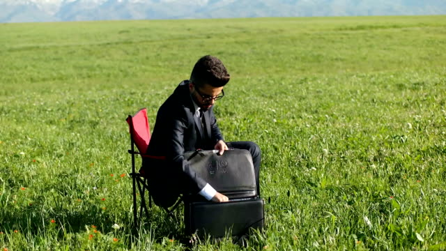 businessman sits in an office chair in a field - working in remote location stock videos & royalty-free footage