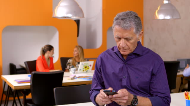 MEDIUM SHOT businessman sits in office texting on smartphone then looks at camera and smiles indoors