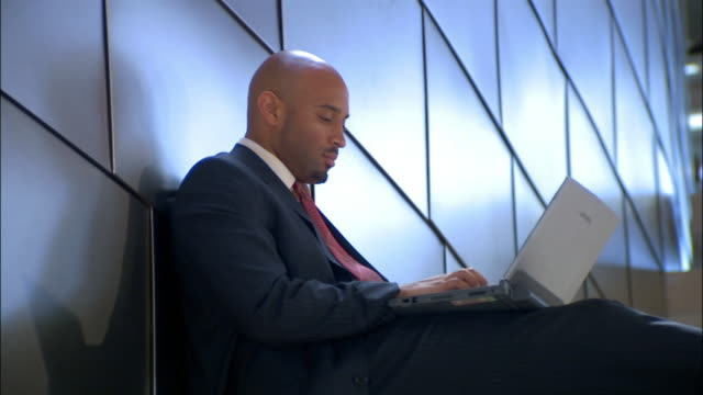 vídeos de stock, filmes e b-roll de businessman sitting against wall typing on laptop computer - só um adulto de idade mediana