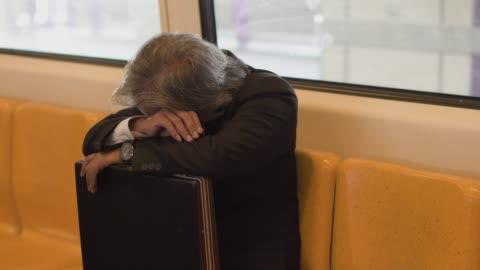 ビジネスマンに座って、電車の中で昼寝をして。 - sleeping点の映像素材/bロール