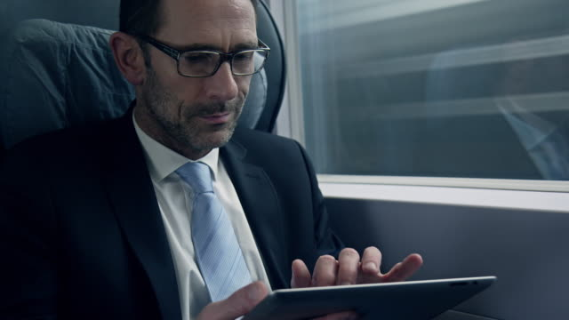 stockvideo's en b-roll-footage met businessman sitting and working in train - ipad