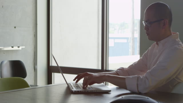 MS PAN Businessman sitting at conference room table working on laptop