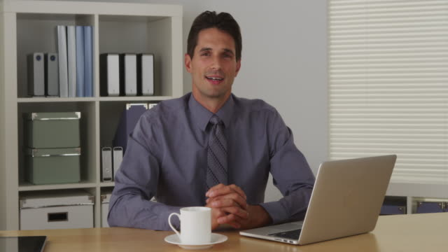 Businessman sitting at desk and talking to camera