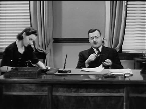 B/W 1940 businessman sitting at desk dictating to woman taking notes in office