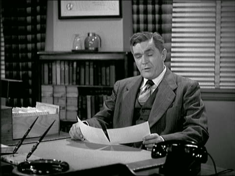 b/w 1948 businessman sitting at desk holding papers + talking to someone off-screen - only mid adult men stock videos & royalty-free footage